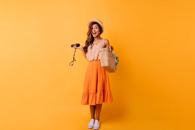 Retrato de corpo inteiro de mulher sensual usa sapatos brancos e chapéu de palha. menina bem vestida caucasiana fazendo caretas na laranja.