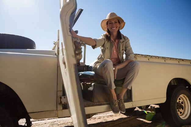 Retrato de corpo inteiro de mulher sentada no veículo
