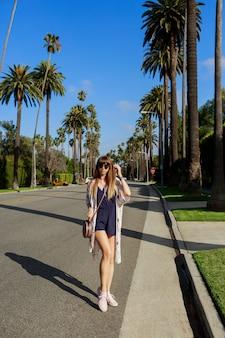 Retrato de corpo inteiro de mulher sorridente elegante andando na rua exótica perto do hotel em um dia quente e ensolarado. passando as férias em los angeles