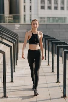 Retrato de corpo inteiro de mulher vestindo terno esportivo e caminhando