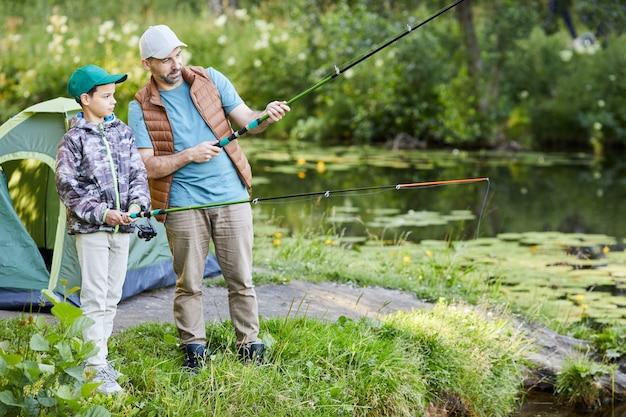 Retrato de corpo inteiro de pai amoroso ensinando filho a pescar enquanto acampam juntos, copie o espaço