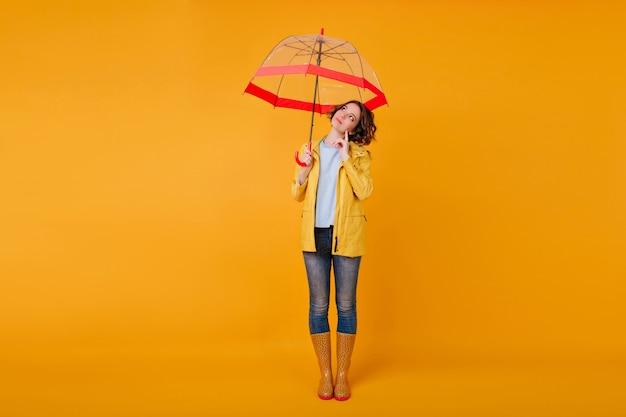 Retrato de corpo inteiro de pensativa menina romântica em pé na parede amarela sob o guarda-sol vermelho. foto de estúdio do elegante modelo feminino em jeans e sapatos de outono, olhando para longe enquanto posava com guarda-chuva.