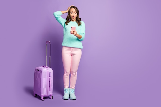 Retrato de corpo inteiro de senhora chateada perdeu o registro de vôo mão na cabeça rolando mala tempo relógio telefone usar calça sapatos rosa pastel de suéter difuso