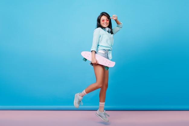 Retrato de corpo inteiro de senhora latina satisfeita em meias rosa, rindo e pulando. mulher hispânica ativa em óculos de sol brincando com o skate.