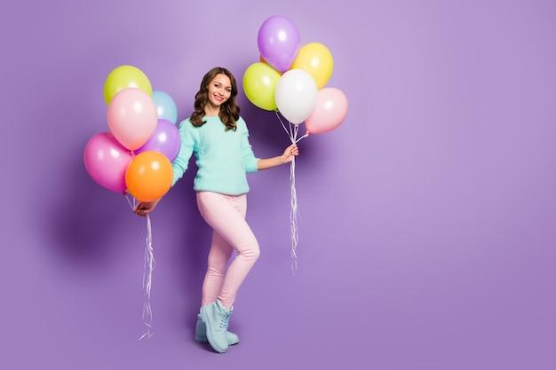 Retrato de corpo inteiro de senhora muito engraçada trazer muitos balões de ar coloridos amigos evento festa de aniversário usar botas de calças pastel rosa suéter difuso.