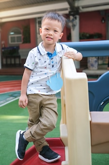 Retrato de corpo inteiro de sorrir asiático 3 - 4 anos de idade menino da criança posar para a câmera durante se divertindo no quadro de escalada no playground