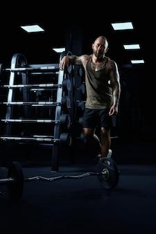 Retrato de corpo inteiro de tenso fisiculturista masculino em roupas esportivas, apoiando-se no carrinho com halteres.