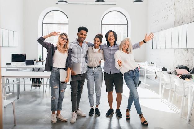 Retrato de corpo inteiro de trabalhador de escritório magro em jeans em pé com as pernas cruzadas perto de um colega asiático. foto interna de um estudante africano alto e uma mulher europeia feliz com o laptop.