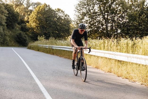 Retrato de corpo inteiro de treinamento de ciclista em ar fresco