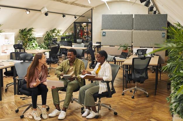 Retrato de corpo inteiro de três empresários contemporâneos discutindo projeto de trabalho enquanto estão sentados em cadeiras em um escritório moderno e sorrindo alegremente, copie o espaço