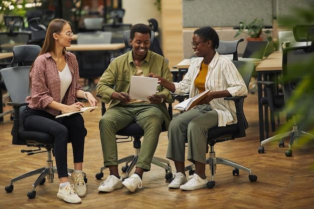 Retrato de corpo inteiro de três empresários contemporâneos discutindo projeto de trabalho enquanto estão sentados em cadeiras em um escritório moderno e sorrindo alegremente