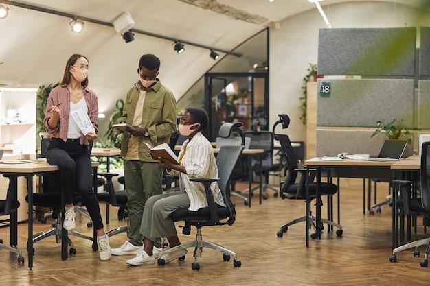 Retrato de corpo inteiro de três empresários contemporâneos usando máscaras enquanto discutem o projeto de trabalho em um escritório moderno pós-pandemia, copie o espaço