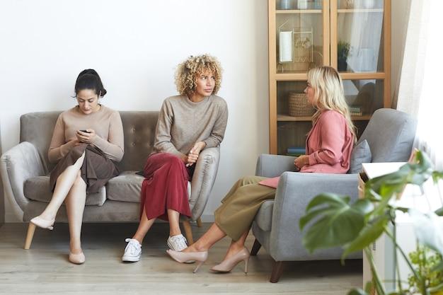 Retrato de corpo inteiro de três mulheres adultas modernas conversando enquanto estão sentadas no sofá durante uma festa interna com amigos