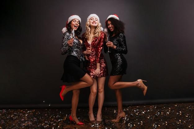 Retrato de corpo inteiro de três mulheres em vestidos comemorando o ano novo