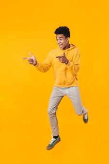 Retrato de corpo inteiro de um adolescente animado pulando isolado na parede amarela, apontando para longe