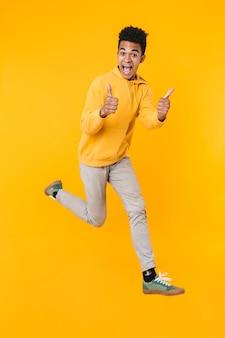 Retrato de corpo inteiro de um adolescente animado pulando isolado sobre uma parede amarela, mostrando os polegares para cima