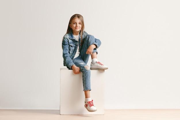Retrato de corpo inteiro de um adolescente bonitinho em roupas jeans elegantes, olhando para a câmera e sorrindo