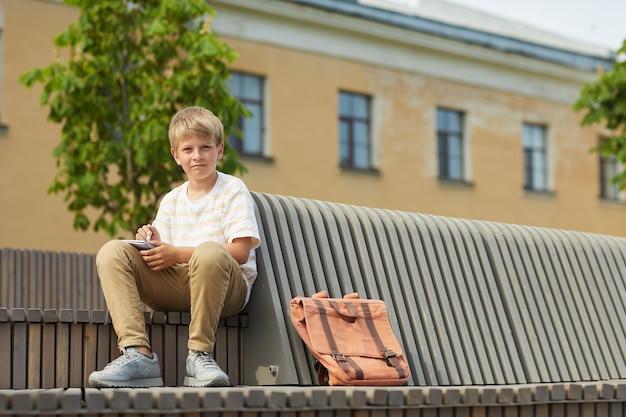 Retrato de corpo inteiro de um adolescente loiro olhando para a câmera enquanto está sentado no banco ao ar livre com uma mochila, copie o espaço