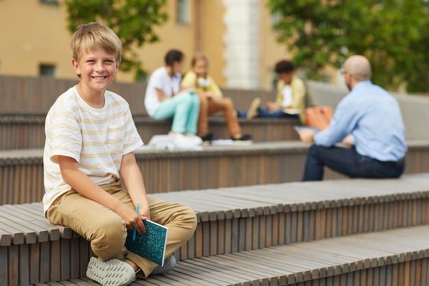 Retrato de corpo inteiro de um adolescente loiro sorrindo para a câmera enquanto está sentado no banco ao ar livre com a professora dando aula no fundo, copie o espaço