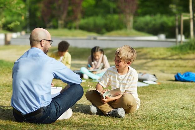 Retrato de corpo inteiro de um adolescente sorridente sentado na grama verde sob a luz do sol e escrevendo no caderno durante a aula ao ar livre com o professor, copie o espaço