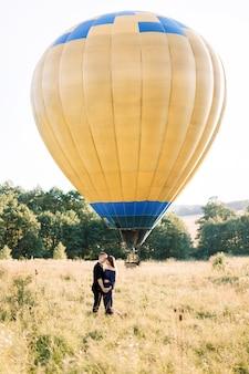 Retrato de corpo inteiro de um adorável jovem casal vestido de preto, abraçando-se e curtindo um passeio de verão no campo, esperando seu passeio de balão de ar