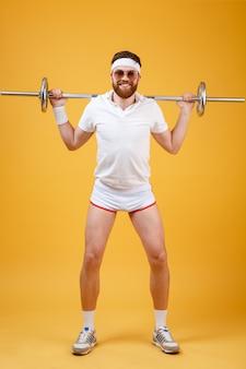 Retrato de corpo inteiro de um atleta de homem exercitar com barra