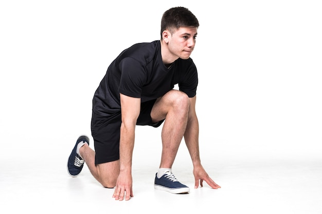 Retrato de corpo inteiro de um atleta do sexo masculino pronto para correr isolado no branco