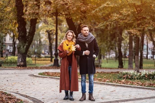 Retrato de corpo inteiro de um casal em um encontro caminhando no parque outono de mãos dadas