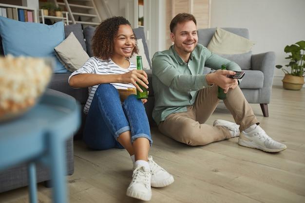 Retrato de corpo inteiro de um casal moderno de raça mista assistindo tv em casa e bebendo cerveja enquanto está sentado no chão de um apartamento aconchegante