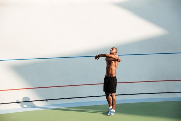 Retrato de corpo inteiro de um desportista apto, esticando as mãos