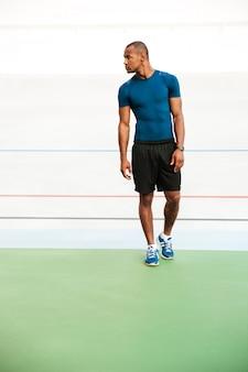 Retrato de corpo inteiro de um desportista muscular apto andando