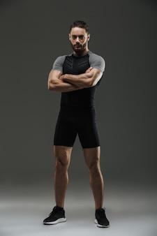 Retrato de corpo inteiro de um desportista muscular confiante