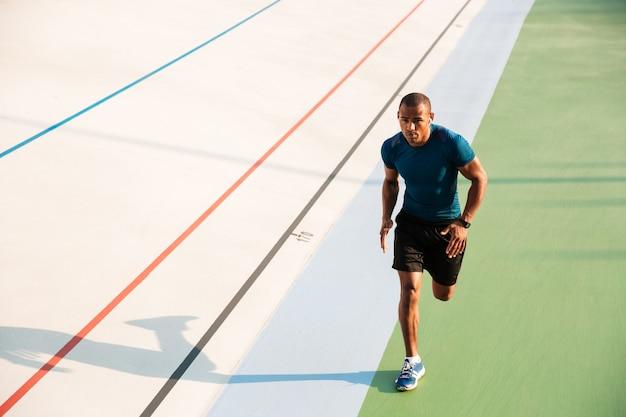 Retrato de corpo inteiro de um desportista muscular correndo
