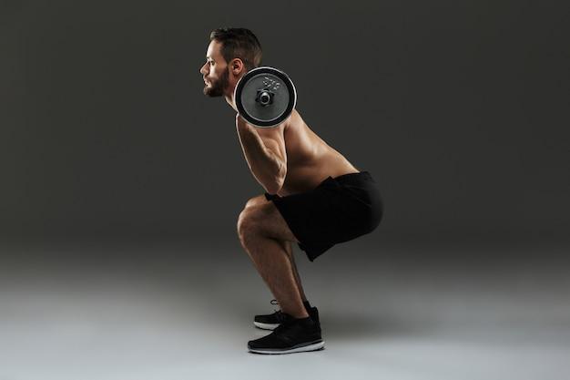 Retrato de corpo inteiro de um desportista muscular sem camisa confiante