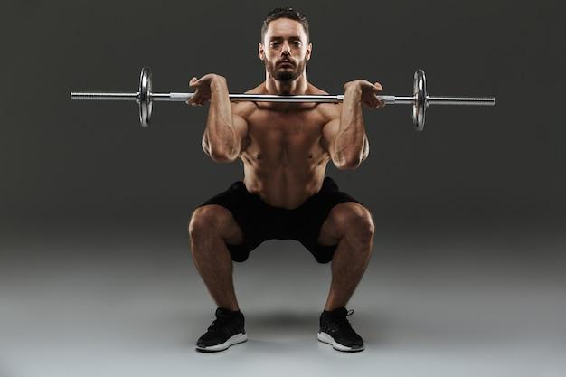 Retrato de corpo inteiro de um desportista muscular sem camisa forte