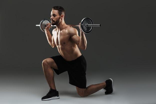 Retrato de corpo inteiro de um desportista muscular sem camisa motivado