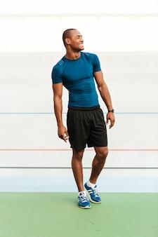 Retrato de corpo inteiro de um desportista musculoso sorridente