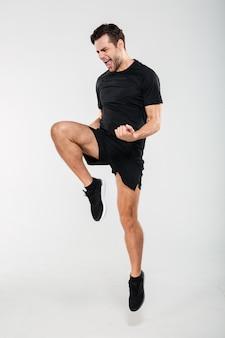 Retrato de corpo inteiro de um desportista satisfeito feliz pulando