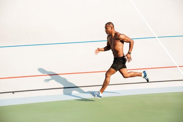 Retrato de corpo inteiro de um desportista seminu forte correndo