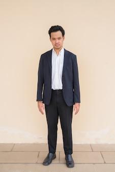 Retrato de corpo inteiro de um empresário asiático vestindo terno contra um fundo simples