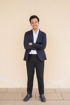 Retrato de corpo inteiro de um empresário asiático vestindo um terno contra um fundo liso com os braços cruzados enquanto sorri