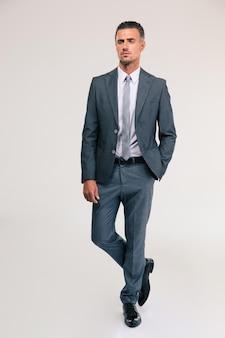 Retrato de corpo inteiro de um empresário bonito de terno andando no espaço cinza