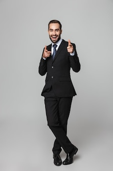 Retrato de corpo inteiro de um empresário bonito e confiante vestindo terno isolado, apontando para a frente