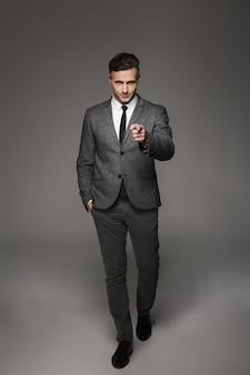 Retrato de corpo inteiro de um empresário elegante vestindo uma fantasia profissional, posando e apontando o dedo em você, isolado sobre uma parede cinza