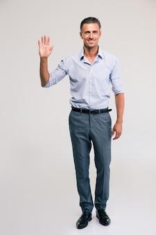 Retrato de corpo inteiro de um empresário feliz, mostrando um gesto de saudação com a palma da mão isolada. olhando para a câmera