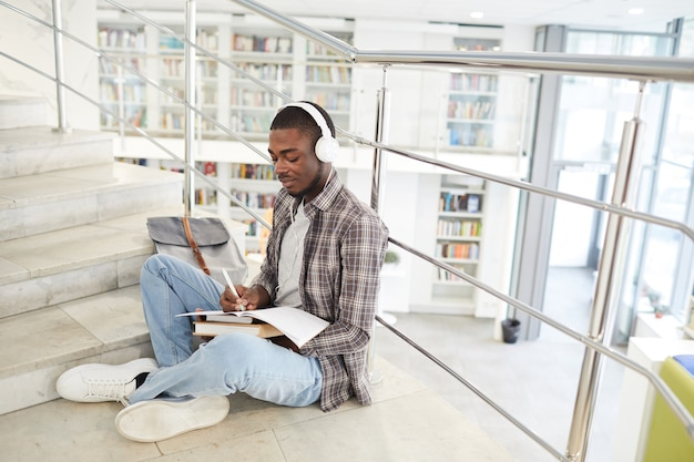 Retrato de corpo inteiro de um estudante afro-americano ouvindo música enquanto está sentado de pernas cruzadas na escada na faculdade e fazendo o dever de casa.