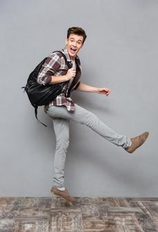 Retrato de corpo inteiro de um estudante do sexo masculino alegre e engraçado pulando na parede cinza