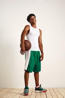 Retrato de corpo inteiro de um feliz alegre atleta musculoso negro segurando uma velha bola de basquete de couro vestindo roupas esportivas verdes e brancas contra uma parede branca e piso de madeira.