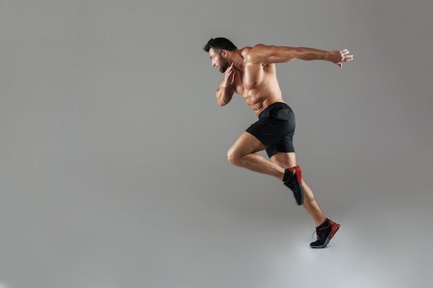 Retrato de corpo inteiro de um fisiculturista masculino sem camisa de ajuste saudável
