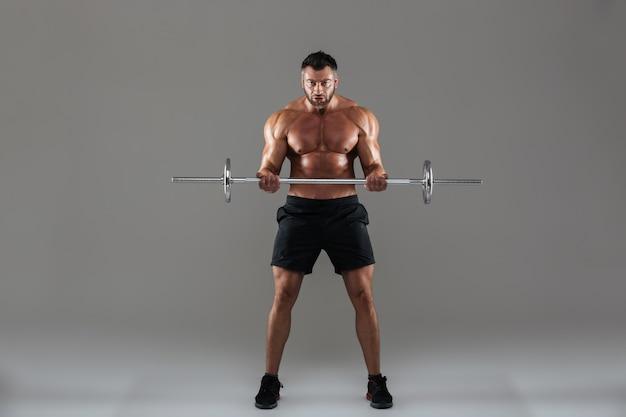 Retrato de corpo inteiro de um fisiculturista masculino sem camisa forte muscular